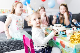 Girl eating cake and looking at camera