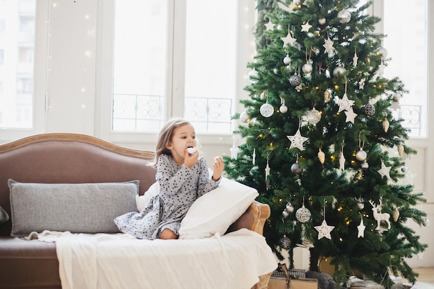 Girl eating cakes, baking, house decorated for new year or christmas, christmas tree, sofa