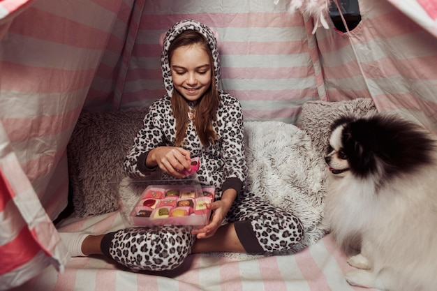 Девушка ест конфеты в палатке в помещении и собака