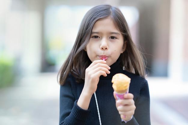 Девушка ест мороженое типа конуса ложкой на открытом воздухе