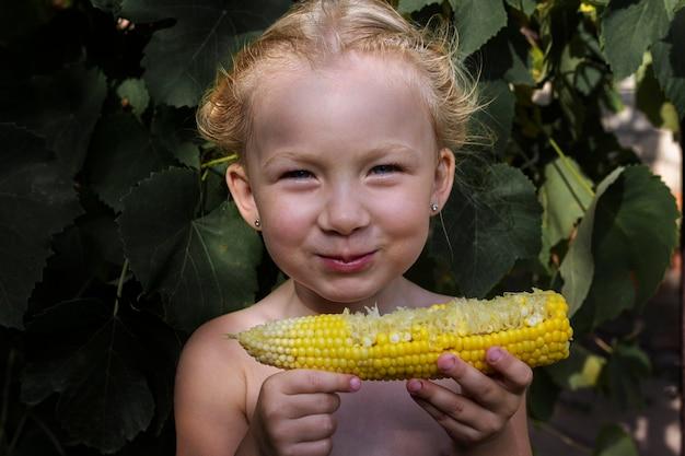 自然光の下で路上でトウモロコシを食べる少女。現実の人間。