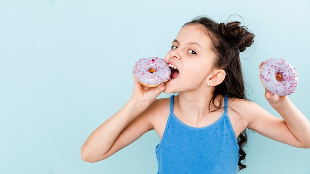 Girl eating delicious doughnuts with copy-space
