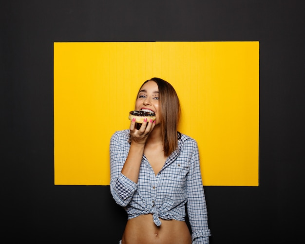 Girl eating donut with chocolate icing