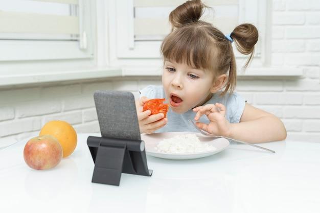 음식을 먹고 스마트 폰에서 만화를 보는 소녀