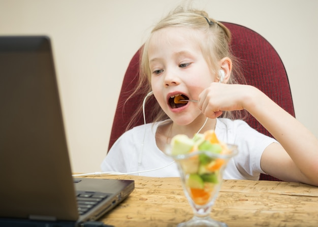 Girl eating fruit cocktail next to the laptop.