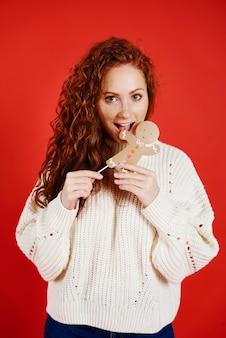 スタジオショットでジンジャーブレッドクッキーを食べる女の子