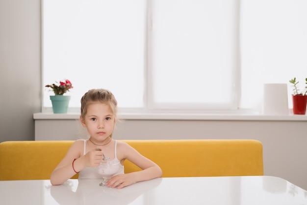테이블에서 아이스크림을 먹는 여자