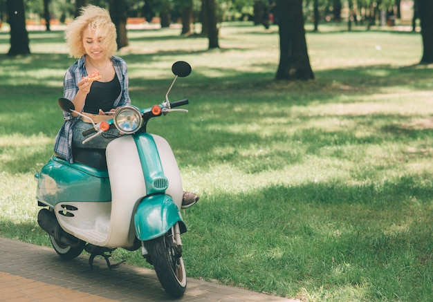 모토 스쿠터 또는 오토바이 먹는 소녀. 모토 스쿠터 또는 오토바이 먹는 소녀. 상자에 뜨거운 피자를 들고 행복 한 젊은 여자. 여자 학생은 시간이 없다, 그는 이동 중에 먹을거야