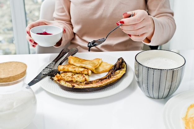 Girl eating pancakes with blueberry jam, breakfast with coffee.