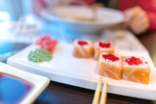 レストランの寿司フィラデルフィアで顔の昼食なしでパスタと寿司を食べる女の子