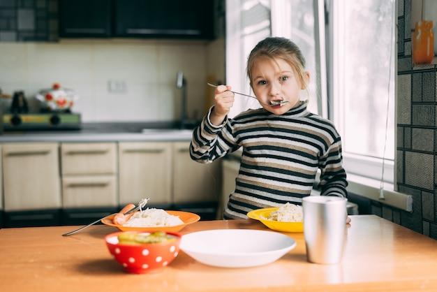 Девушка ест макароны с колбасой на кухне в полосатой куртке