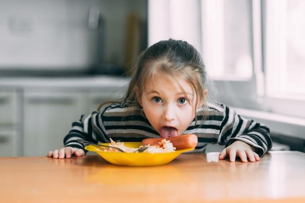 스트라이프 재킷에 부엌에서 소시지와 파스타를 먹는 소녀