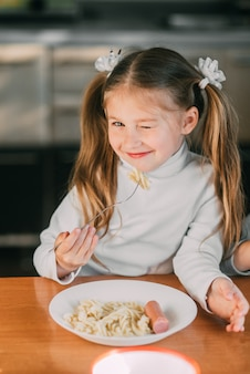 Girl eating pasta with sausage in the kitchen in a striped jacket