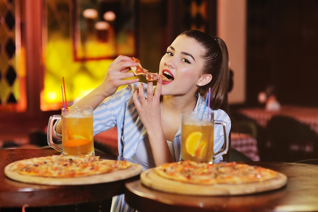 Girl eating pizza and drinking beer or a beer citrus cocktail on the background of a bar or pizzeria.