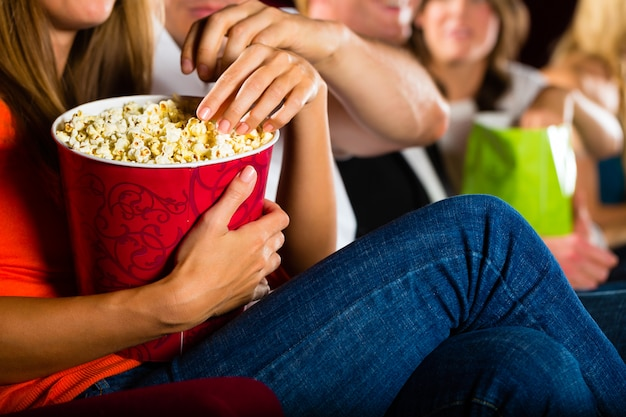 Girl eating popcorn in cinema or movie theater