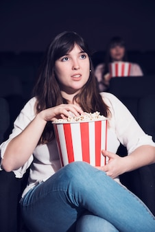 Girl eating popcorn in cinema