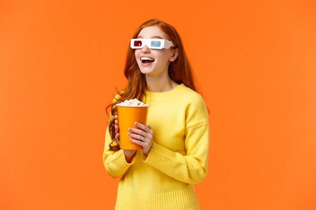 Девушка ест попкорн, улыбаясь, удивлен, глядя на большой экран, смотреть фильм в кино