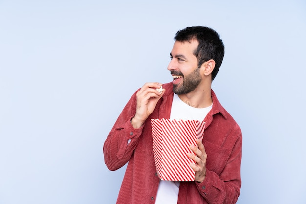 Girl eating popcorn while watching a movie over isolated wall