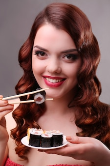 Girl eating sushi with a chopsticks