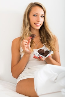 Girl eating sweet chocolate on white sheet