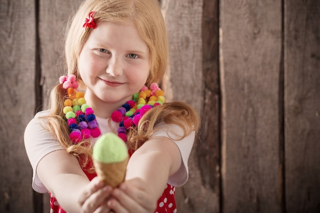 Girl eating tasty ice cream over wooden wall