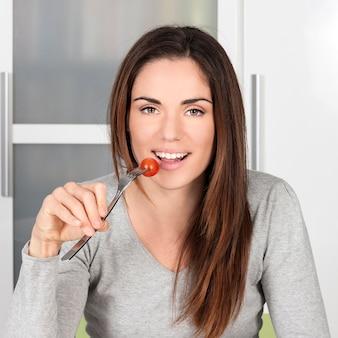 Ragazza che mangia pomodoro a casa