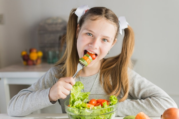 Girl eating vegetable salad with fork