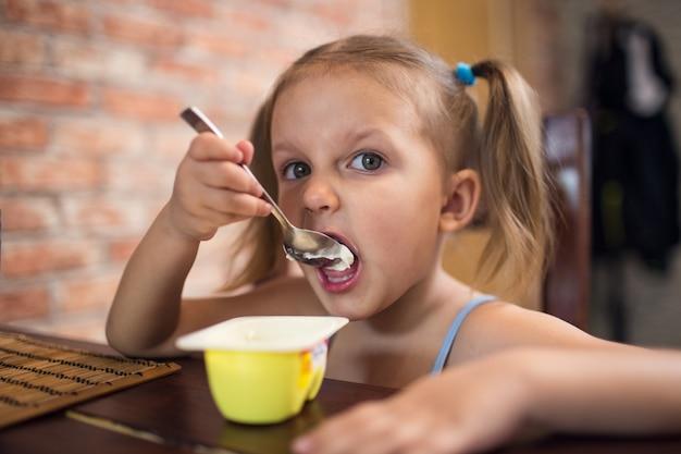 테이블에서 요구르트를 먹는 소녀