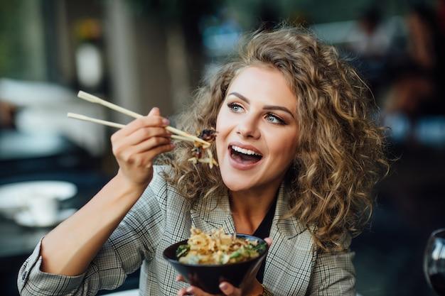 女の子は電化製品を食べます。仕事帰りのジャケットを着た女の子が食べる。女性はチョップスティックでシーフードを食べる。