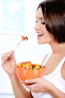 女の子は新鮮な野菜サラダを食べる
