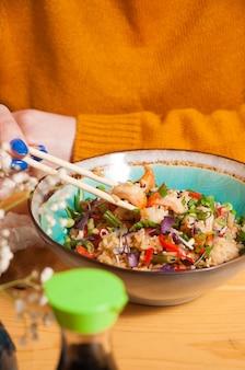 A girl eats garlic rice with shrimp in a restaurant