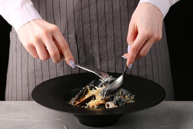 소녀는 이탈리아 파스타를 먹는다. 해산물과 검은 파스타. 숟가락과 포크로 먹는 파스타.