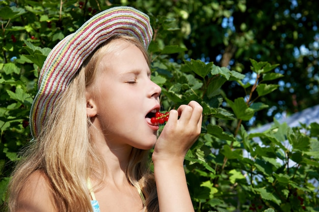 Girl eats red currant in the garden