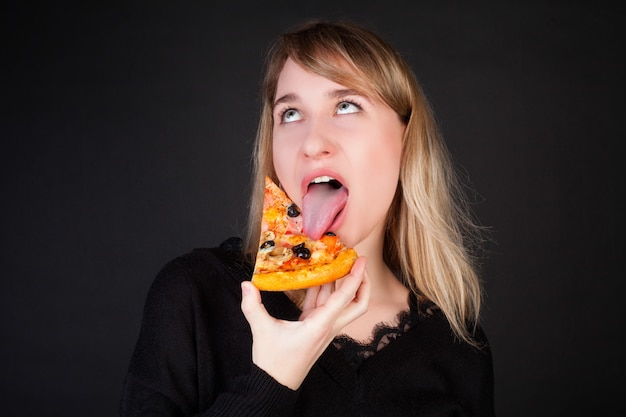 The girl eats a slice of pizza and makes a face, on a black background.
