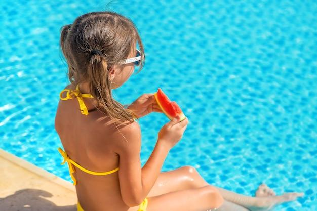 女の子はプールサイドでスイカを食べる