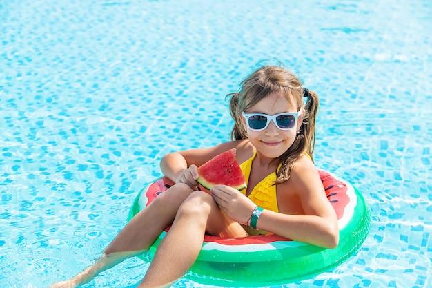 女の子はプールで膨らませることができるスイカでスイカを食べる