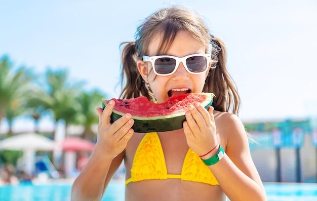 女の子はプールの中でスイカを食べる