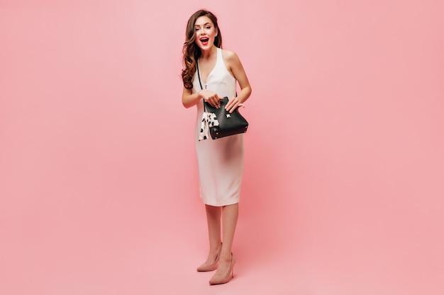 Girl in elegant dress opens black handbag and looks into camera on pink background.