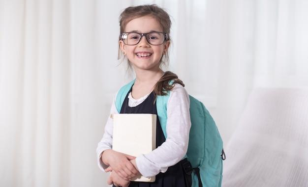 Девочка-ученица начальной школы с рюкзаком и книгой