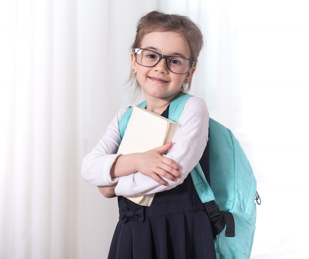 Girl-elementary school student with a backpack and a book