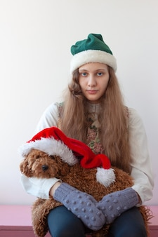 A girl in an elf hat holds a poodle in a santa claus hat in her arms.