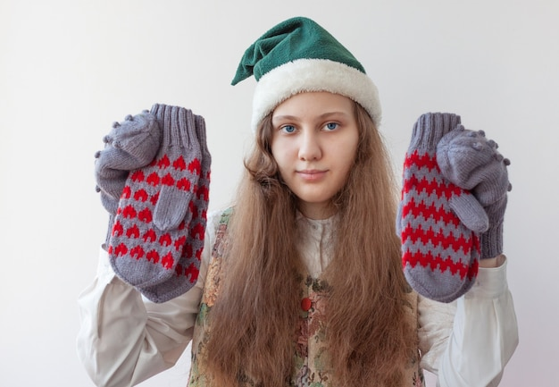 A girl in an elf hat holds several knitted mittens in her hands.