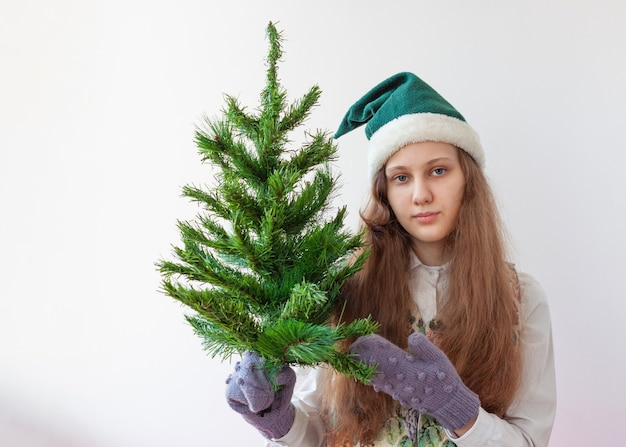 A girl in an elf hat holds a small artificial christmas tree in her hands.