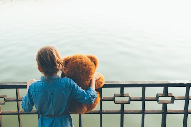 Девушка обнимает милый плюшевый мишка смотрит на озеро