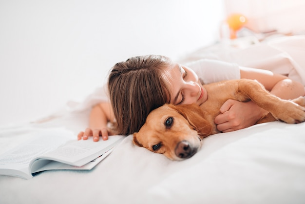 Girl embracing dog on the bed