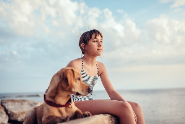 Girl embracing her dog while sitting on the rock by the sea
