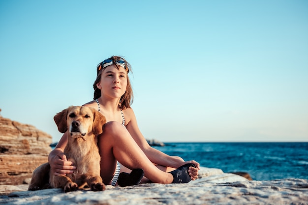 Girl embracing her dog while sitting on the rocky beach