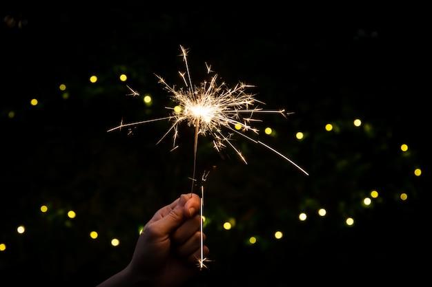 Девушке нравится играть с маленьким бенгальским огнем, празднуя в рождество и новый год фестиваль.