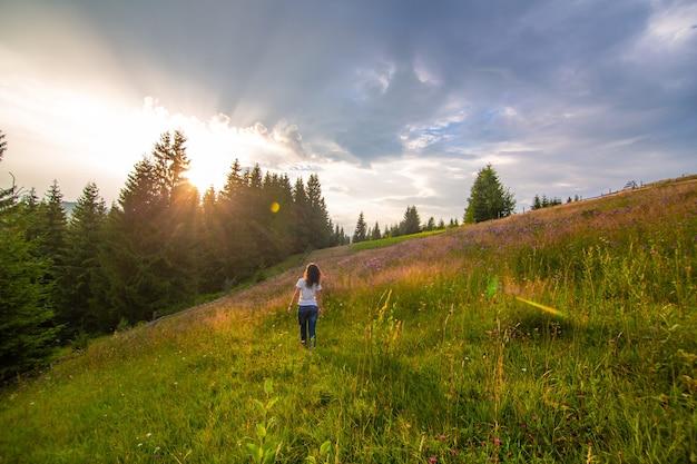 女の子は純粋な自然を楽しんでいます。夕日に会うためにフィールドの上を歩きます。