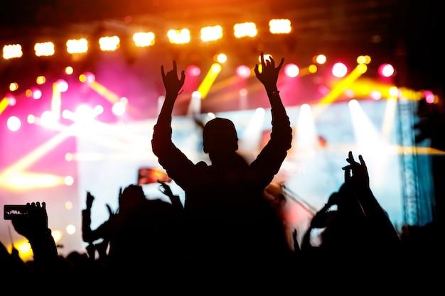 音楽祭やコンサートを楽しんでいる女の子。群衆の黒いシルエット。